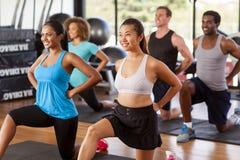 舒展在健身房的不同种族的小组 库存图片