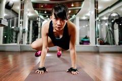 舒展在健身房的亚裔健身女孩 库存照片
