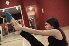 舒展在健身房的十几岁的女孩腿 免版税库存图片