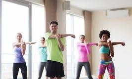 舒展在健身房的小组微笑的人民 免版税库存照片