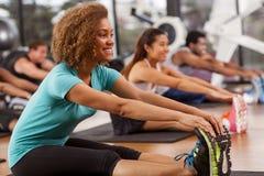 舒展在健身房的少妇 免版税库存图片