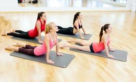 舒展在健身房的席子的小组微笑的妇女 免版税库存照片