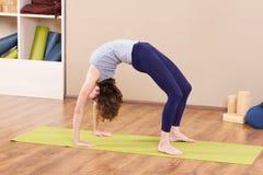 舒展在健身房的年轻运动的妇女 图库摄影