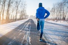 舒展在冬天公园的赛跑者 健康生活方式 图库摄影