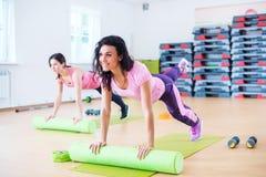 舒展在地板上的适合的妇女使用做板条锻炼的泡沫路辗 免版税图库摄影