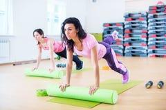 舒展在地板上的适合的妇女使用做板条锻炼的泡沫路辗 库存照片