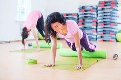 舒展在地板上的适合的妇女使用做板条锻炼,俯卧撑的泡沫路辗 图库摄影