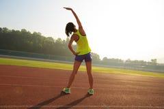 舒展在奔跑前的妇女赛跑者早晨在体育场轨道的晴朗的 库存图片