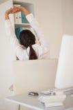 舒展在她的书桌的偶然女实业家 免版税库存照片
