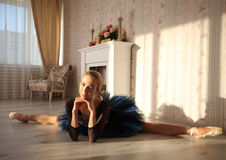 舒展在家庭内部,在地板上的分裂的美丽的少妇芭蕾舞女演员 库存图片