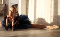 舒展在家庭内部,在地板上的分裂的美丽的少妇芭蕾舞女演员 免版税库存照片