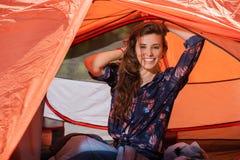 舒展在帐篷的愉快的旅游女孩微笑 免版税库存图片