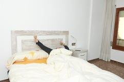 舒展在床上的妇女在醒以后 免版税库存图片