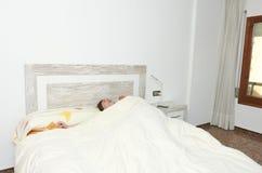 舒展在床上的妇女在醒以后 免版税库存照片