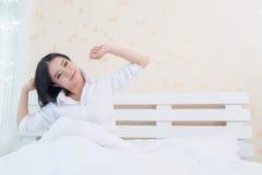 舒展在床上的妇女以后醒,后面看法 库存图片