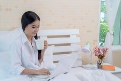 舒展在床上的妇女以后醒 亚裔妇女是醒的在床上 免版税库存照片