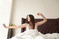 舒展在床上的愉快的逗人喜爱的妇女早晨 免版税库存图片