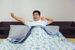舒展在床上的Â亚洲人以后醒 库存图片