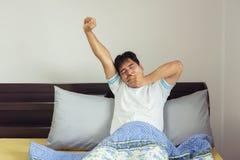 舒展在床上的Â亚洲人以后醒 库存照片