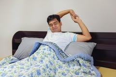 舒展在床上的Â亚裔人以后醒 免版税图库摄影