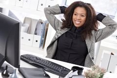舒展在服务台微笑的美丽的女实业家 库存图片