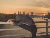 舒展在桥梁的健身妇女腿在日出 免版税库存图片