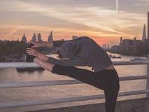 舒展在桥梁的健身妇女腿在日出 免版税库存照片
