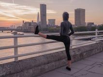 舒展在桥梁的健身妇女腿在日出 图库摄影