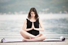 舒展在海滩海边的瑜伽席子的适合的健康妇女,做锻炼胃肠咬嚼、训练和生活方式 免版税图库摄影
