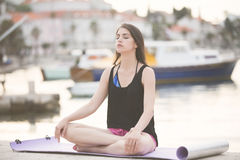 舒展在海滩海边的瑜伽席子的适合的健康妇女,做锻炼胃肠咬嚼、训练和生活方式 免版税库存图片