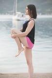舒展在海滩海边的瑜伽席子的适合的健康妇女,做锻炼胃肠咬嚼、训练和生活方式 免版税库存照片