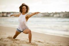 舒展在海滩的混杂种族舞蹈家 免版税库存照片