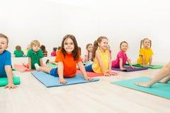 舒展在瑜伽席子的孩子后面在体育俱乐部 免版税库存图片