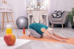 舒展在瑜伽席子的运动资深妇女 库存图片