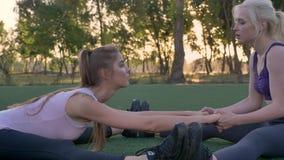 舒展在足球场在公园,早晨的两名年轻俏丽的妇女解决,减重 股票录像