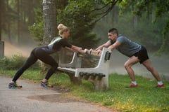 舒展在跑前的年轻夫妇在树木繁茂的森林里 免版税库存图片