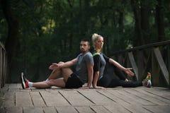 舒展在跑前的年轻夫妇在树木繁茂的森林里 免版税图库摄影