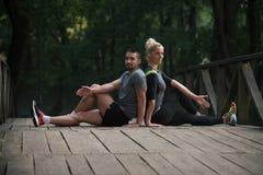 舒展在跑前的年轻夫妇在树木繁茂的森林里 免版税库存照片