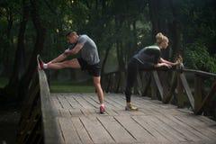 舒展在跑前的年轻夫妇在树木繁茂的森林里 库存图片