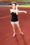 舒展在跑步前的亚裔运动员 免版税库存图片