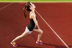 舒展在运动场的中国女性athelete腿,温暖 图库摄影