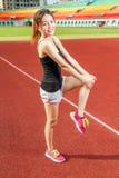 舒展在运动场的中国女性athelete腿,温暖 免版税库存照片