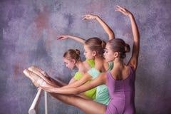 舒展在酒吧的三位年轻芭蕾舞女演员 免版税图库摄影