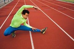 舒展在锻炼前的公赛跑者 库存图片