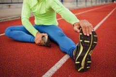 舒展在锻炼前的公赛跑者 免版税图库摄影