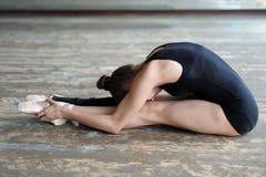 舒展坐地板的跳芭蕾舞者 免版税库存照片