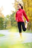 舒展大腿的赛跑者妇女 免版税库存照片