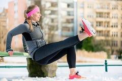 舒展她的体育的妇女肢体在冬天行使 库存照片