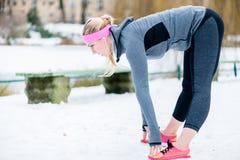 舒展她的体育的妇女肢体在冬天行使 库存图片