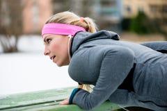 舒展她的体育的妇女肢体在冬天行使 免版税库存图片